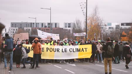 anti macron : STRASBOURG, FRANCE - DEC 8, 2018: Crowd of people preparing to march in Central Strasbourg at the nationwide protest Marche Pour Le Climate with large yellow palcard Stock Footage