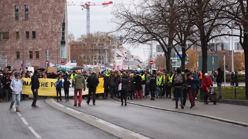 anti macron : STRASBOURG, FRANCE - DEC 8, 2018: Front view of crowd of people marching in Central Strasbourg at the nationwide protest Marche Pour Le Climate with large yellow palcard