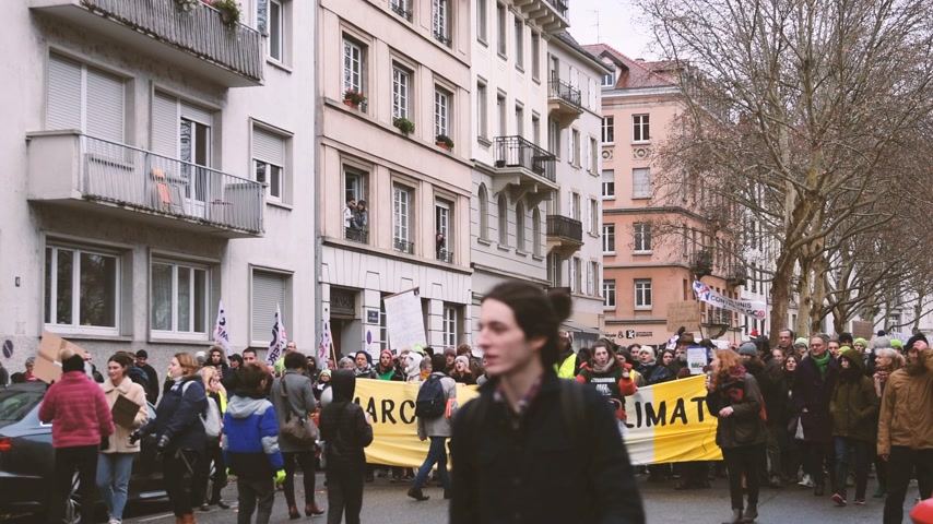 anti macron : STRASBOURG, FRANCE - DEC 8, 2018: Side view of large crowd of people marching in Central Strasbourg at the nationwide protest Marche Pour Le Climate with large yellow palcard