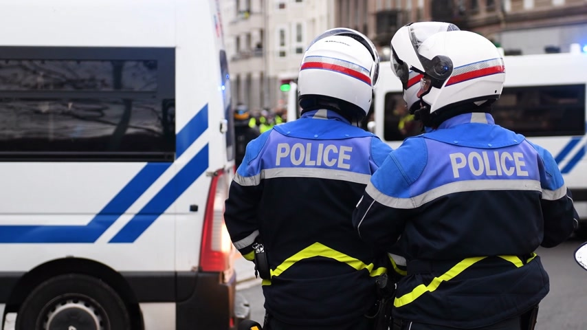french team : STRASBOURG, FRANCE - DEC 8, 2018: Rear view of French equipped police officers securing the zone in front of the Yellow vests movement protesters on Quai des Bateliers street Stock Footage