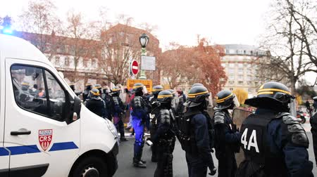 french team : STRASBOURG, FRANCE - DEC 8, 2018: Rear view of police officers securing the zone in front of the Yellow vests movement protesters on Quai des Bateliers street - black and white