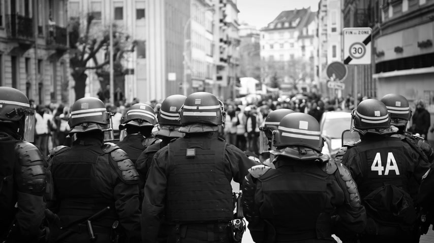 protesto : STRASBOURG, FRANCE - DEC 8, 2018: Police officers securing the zone in front of the Yellow vests movement protesters on Quai des Bateliers street black and white