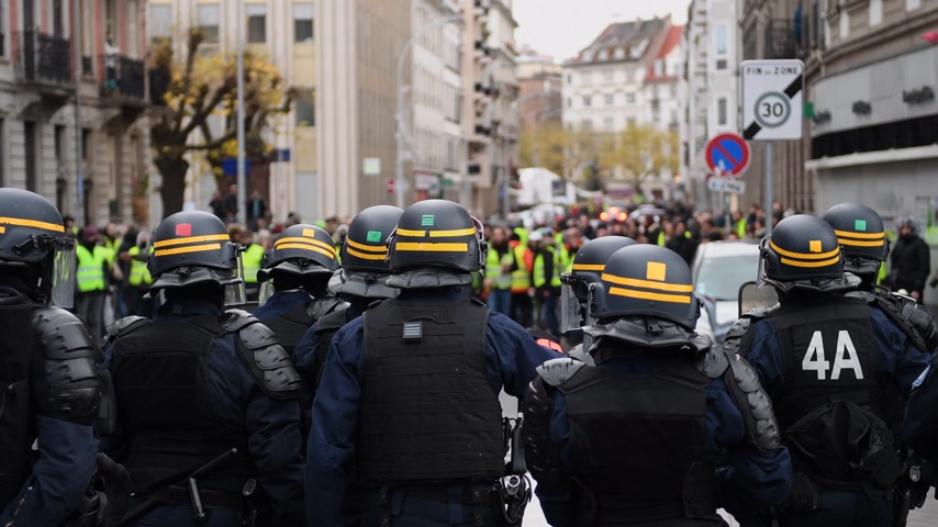 dispute : STRASBOURG, FRANCE - DEC 8, 2018: Police officers securing the zone in front of the Yellow vests movement protesters on Quai des Bateliers street