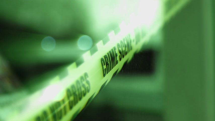 matança : Police scene do not cross sign on the window of a store where murder thief has took place - reflection of blue siren lights defocused in the window iridescent green beam lights Stock Footage