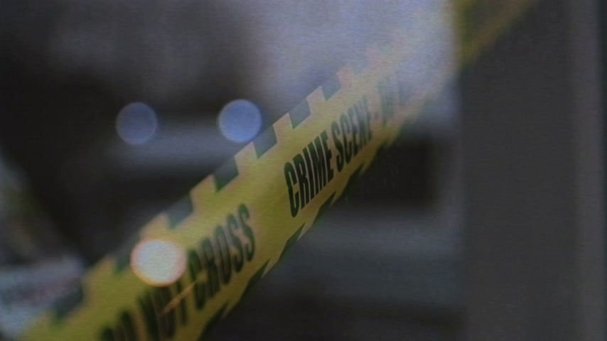 forensic : Police scene do not cross sign on the window of a store where murder thief has took place - reflection of blue siren lights defocused in the window vhs tape film effect of a crime scene Stock Footage
