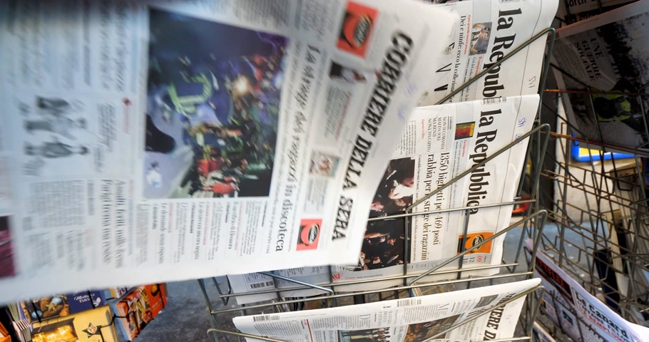 semanal : PARIS, FRANCE - DEC 10, 2018: Newspaper stand kiosk stand selling Italian press Corriere Della Sera with title on cover about Six dead and dozens hurt in nightclub stampede in Italy Vídeos