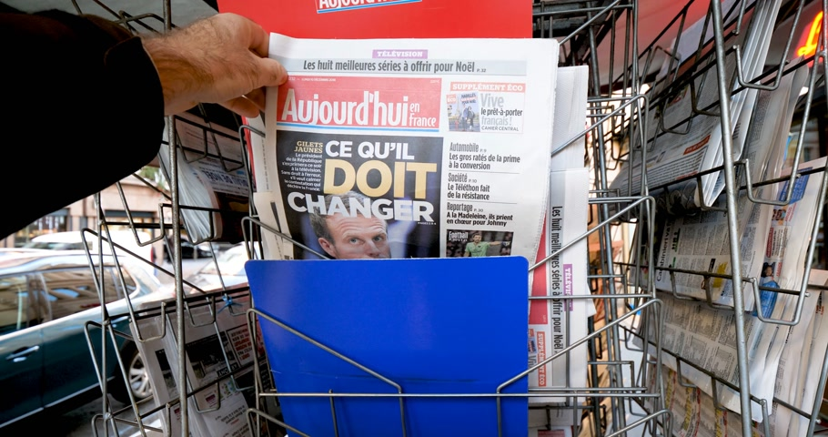 weekly : PARIS, FRANCE - DEC 10, 2018: Newspaper stand kiosk stand selling press with man buying Aujourdhui Today newspaper featuring Emmanuel Macron on the front page