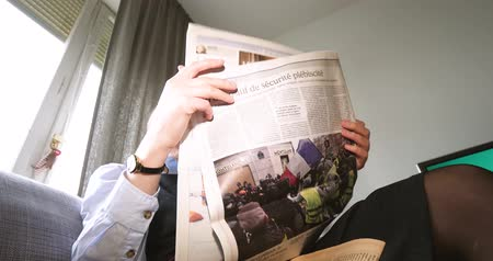 times : PARIS, FRANCE - DEC 10, 2018: Woman reading latest Le Figaro newspaper in living room with main image on cover about Yellow Vests protest in France Stock Footage