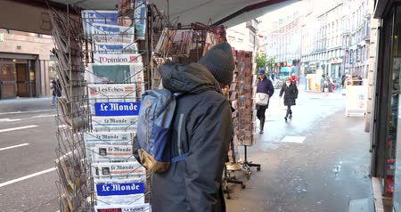 french media : PARIS, FRANCE - DEC 10, 2018: Rear view of adult man at newspaper stand kiosk stand selling press with multiple French newspapers, lOpinion, Express, Le monde, Le figaro, Monde Economique, Les Echos, La Tribune