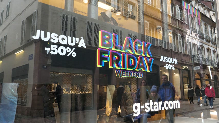 pitka : PARIS, FRANCE - CIRCA 2018: Black Friday sale sign in the showcase store window of a modern shopping facade on a pedestrian street with reflection of customers people