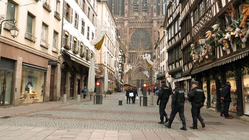 anti terrorism : STRASBOURG, FRANCE - DEC 11, 2018: Police officers and few pedestrians locals and tourists visiting Rue Merciere after terrorist attack in the Strasbourg Christmas market area with Notre-Dame Cathedral in background Stock Footage