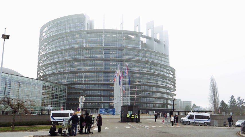 symbol of respect : STRASBOURG, FRANCE - DEC 11, 2018: Journalist reporting live from European Parliament with European Union and French Flags flies at half-mast in front of the European Parliament following an attack during annual Christmas Market Stock Footage