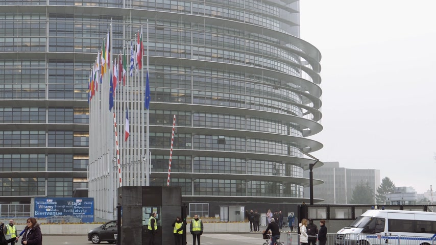 flag half mast : STRASBOURG, FRANCE - DEC 11, 2018: Facade of European Parliament with European Union and French Flags flies at half-mast following an attack in center of Strasbourg during annual Christmas Market