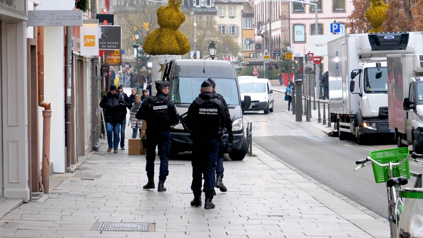 policista : STRASBOURG, FRANCE - DEC 11, 2018: Rear view of armed police officers gendarmerie gendarmes surveilling city center after the terrorist attack in the Strasbourg Christmas market area Dostupné videozáznamy