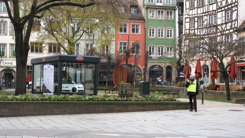 anti terrorism : STRASBOURG, FRANCE - DEC 11, 2018: Armed police officers surveilling city center after the terrorist attack in the Strasbourg Christmas market area with Bugatti supercar in background Stock Footage