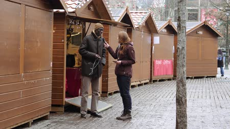 anti terrorism : STRASBOURG, FRANCE - DEC 11, 2018: Female journalist interviewing black ethnicity man neat Christmas chalet in Place Kleber after terrorist attack in Strasbourg Stock Footage