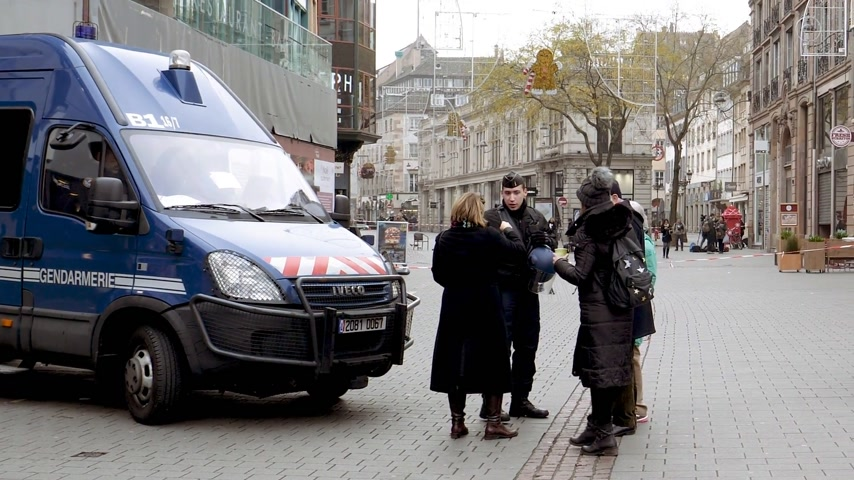 anti terrorism : STRASBOURG, FRANCE - DEC 11, 2018: Women in front of Police French vans and Police officers securing Place Kleber square near crime scene after an attack in the Strasbourg Christmas market area