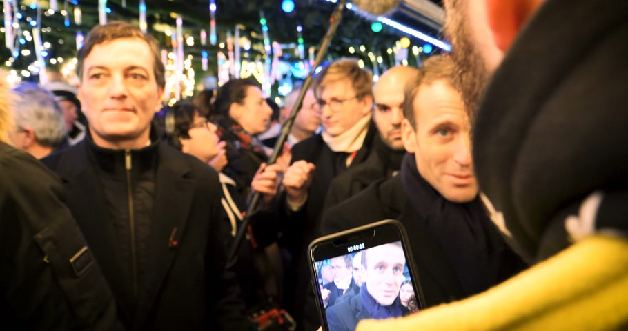 líder : STRASBOURG, FRANCE - DEC 14, 2018: Handheld video of smiling French President Emmanuel Macron shakes hands with members of a crowd at Christmas Market after paying tribute for victims of terrorist attack on 11 December