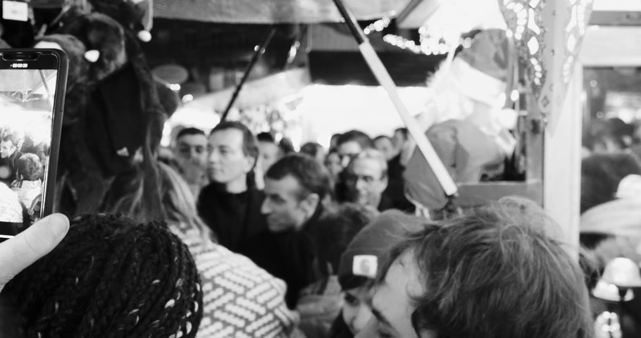symbol of respect : STRASBOURG, FRANCE - DEC 14, 2018: Handheld video of French President Emmanuel Macron shakes hands with members of a crowd at Christmas Market