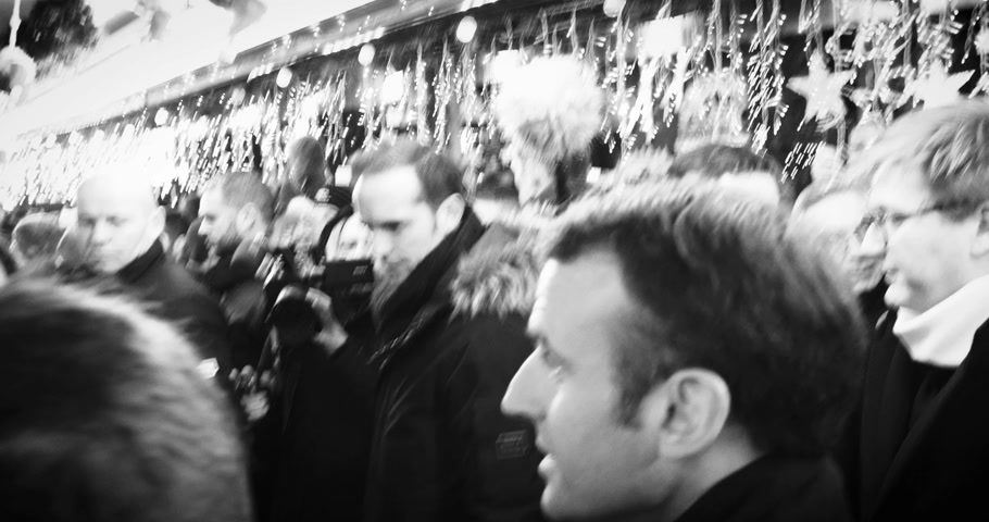 президент : STRASBOURG, FRANCE - DEC 14, 2018: Smiling French President Emmanuel Macron shakes hands with members of a crowd at Christmas Market after paying tribute for victims of terrorist attack on 11 December - black and white