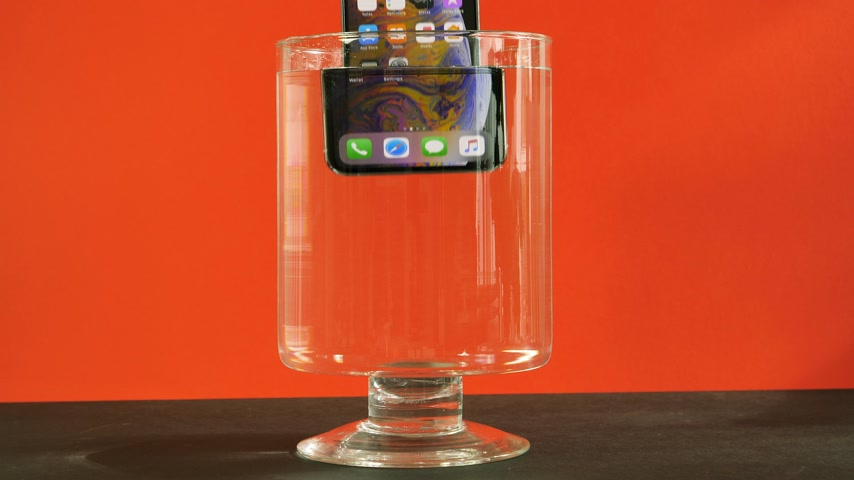 deset : PARIS, FRANCE - CIRCA 2018: Man immersing new Apple Computers iPhone Xs Max smart phone with all home apps on display in water against red background