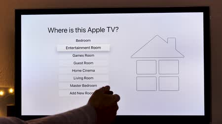 remote location : PARIS, FRANCE - NOV 2018: Man unboxing installing connecting the latest Apple TV 4K device by Apple Computers to Panasonic Plasma OLED tv in living room where is this Apple Tv