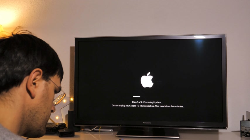 güncelleştirme : PARIS, FRANCE - NOV 2018: Man updating the latest Apple TV 4K device by Apple Computers to Panasonic Plasma OLED tv in living room Stok Video