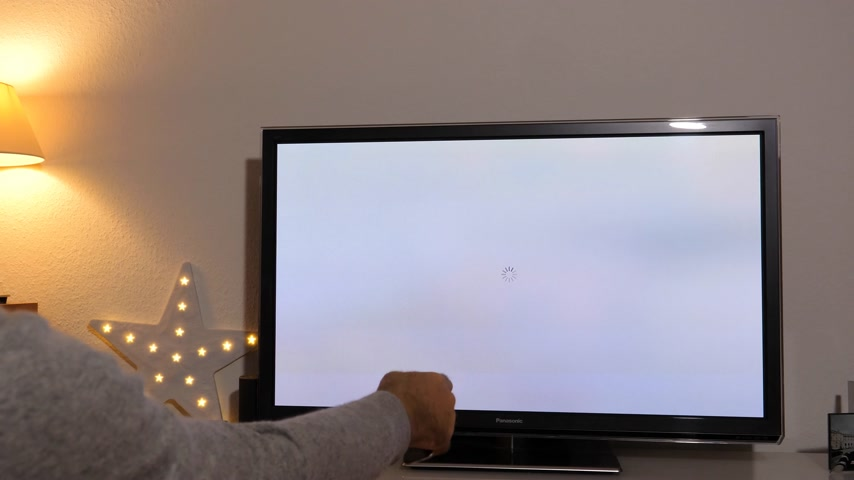 activating : PARIS, FRANCE - NOV 2018: Man activating latest Apple TV 4K device by Apple Computers to Panasonic Plasma OLED tv in living room