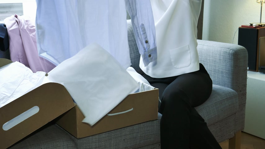 receber : French fashionable woman unpacking unboxing new cardboard with multiple clothes shoes on the living room sofa - online shopping for the blue business silk shirt Stock Footage