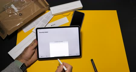 latest : PARIS, FRANCE - NOV 16, 2018: Man using Apple Music app on latest iPad Pro smart tablet device and Apple Pencil 2 in modern office environment
