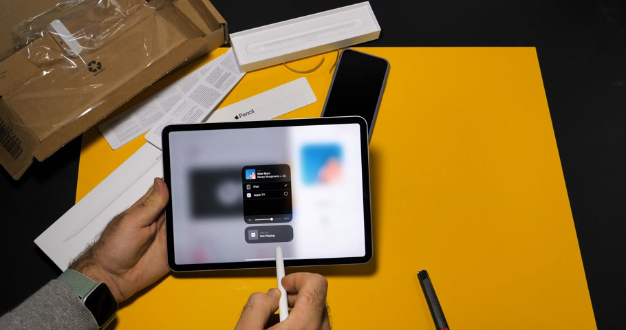 apple computers : PARIS, FRANCE - NOV 16, 2018: Man testing sending via Airplay from new iPad Pro smart tablet device to Apple TV a song from Apple Music