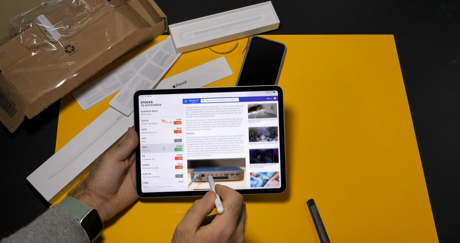 macintosh : PARIS, FRANCE - NOV 16, 2018: Man unboxing latest iPad Pro smart tablet device and Apple Pencil 2 manufactured by Apple Computers in modern office environment yellow table all applications time lapse fast motion