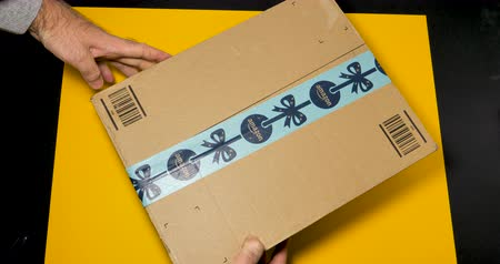 отправка : PARIS, FRANCE - CIRCA 2018: Above POV unboxing unpacking with cutter the holiday Amazon Cardboard box against yellow background. Amazon Prime is the online paid subscription service offered by Amazon.com web-commerce site