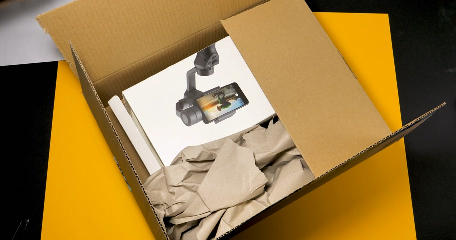 eliminer : PARIS, FRANCE - circa 2018: Curious man unboxing déballage nouveau DJI Osmo Mobile 2 Smartphone Gimbal fabriqué par la société SZ DJI Technology Co., Ltd