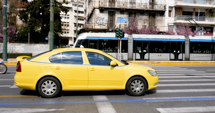 athene : ATHENS, GREECE - CIRCA 2018: Metro trains, cars and buses on a busy Athens street in the morning with woman waiting to cross the street