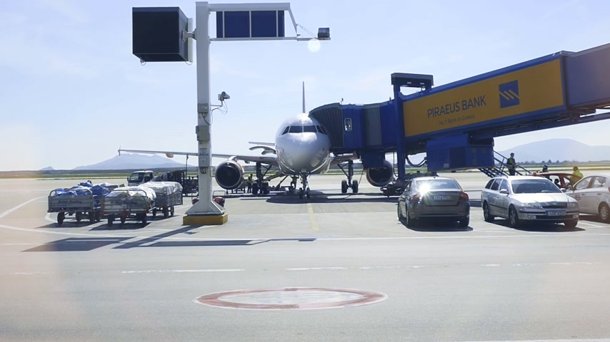 tarmac : ATHENS, GREECE - CIRCA 2018: Workers exit modern airplane aircraft after inspection before a new destination secured flight with new jet bridge and advertising to Piraeus bank -  slow motion blue color cast