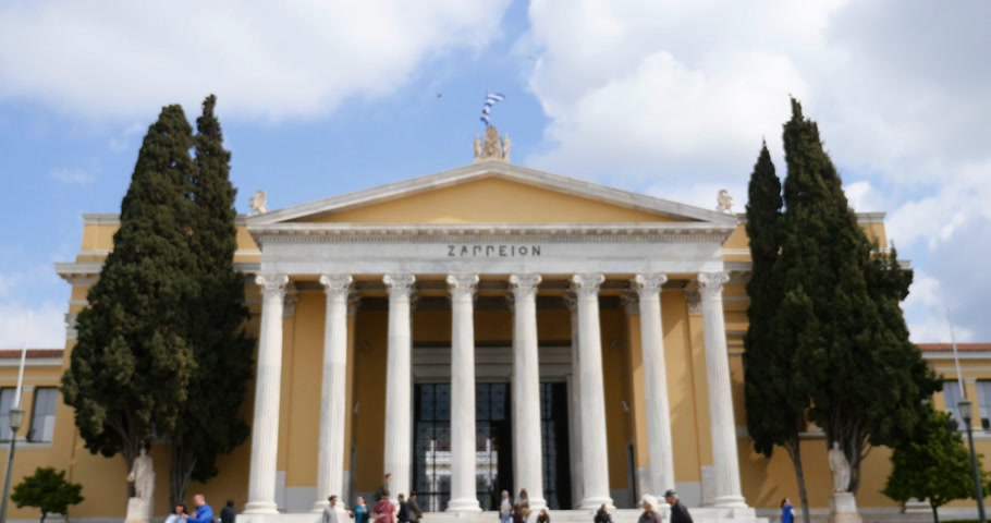 greek flag : Handheld defocused video of people in front of The Zappeion Megaro the building in the National Gardens of Athens in the heart of Athens, Greece used for meetings and ceremonies