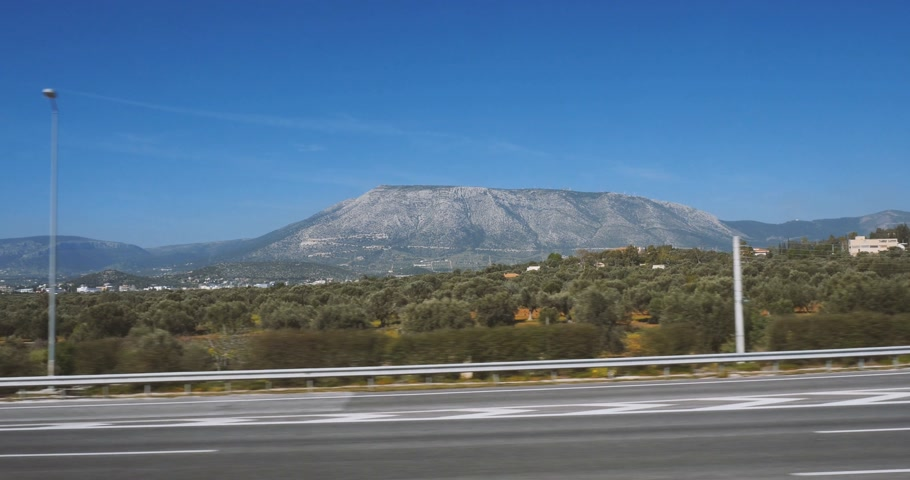 toll : Discovering Athens, Greece view from the train window to the almost empty Attiki Odos highway privately owned toll motorway, buildings and mountains