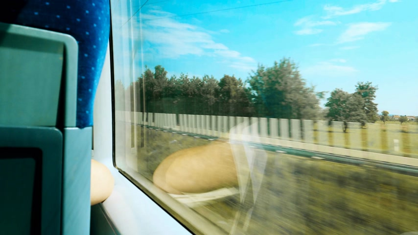 first class : Rear view of woman silhouette reflection travel in fast German train with window view of German landscape with highway passing nearby Stock Footage