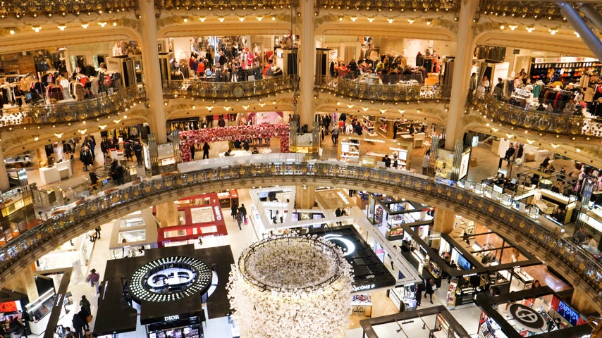 ismert : PARIS, FRANCE - CIRCA 2019: Aerial drone pan over the Art Nouveau interior of luxury fashionable interior of Galeries Lafayette with thousands of customers shopping for world known brand