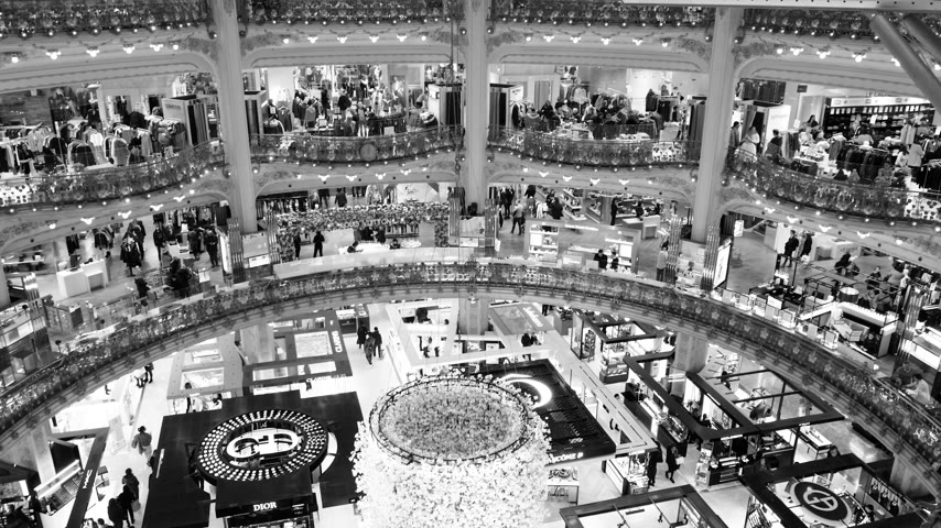 известное место : PARIS, FRANCE - CIRCA 2019: Black and white footage aerial drone pan over the Art Nouveau interior of luxury fashionable interior of Galeries Lafayette with thousands of customers shopping for world known brand Стоковые видеозаписи