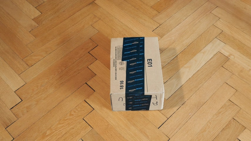 отправка : PARIS, FRANCE - SEP 28, 2018: Focusing to Amazon Cardboard box parcel on parquet wooden floor ready for unboxing Amazon Prime is the online paid subscription service offered by Amazon.com web-commerce site