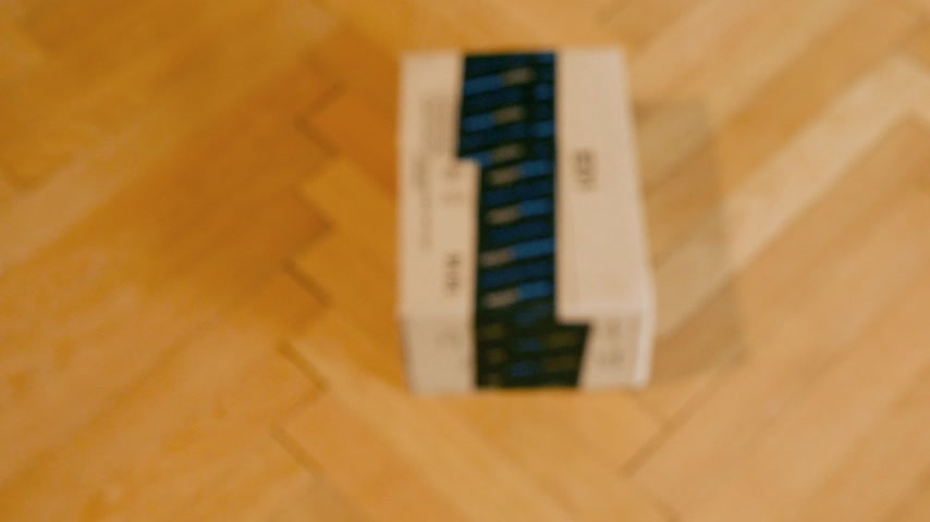 znak : PARIS, FRANCE - SEP 28, 2018: Slow focus to freshly received Amazon Cardboard box parcel on parquet wooden floor ready for unboxing Amazon Prime is the online paid subscription service offered by Amazon.com web-commerce site Wideo