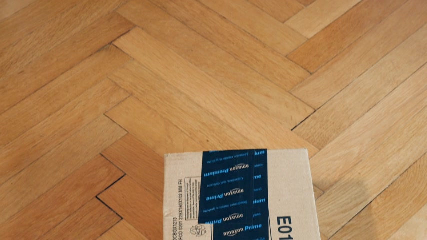 паркет : PARIS, FRANCE - SEP 28, 2018: Tilt-down to freshly received Amazon Cardboard box parcel on parquet wooden floor ready for unboxing Amazon Prime is the online paid subscription service offered by Amazon.com web-commerce site