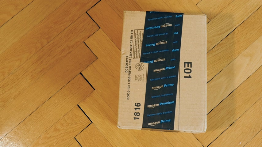 odeslání : PARIS, FRANCE - SEP 28, 2018: Motion over freshly received Amazon Cardboard box parcel on parquet wooden floor ready for unboxing Amazon Prime is the online paid subscription service offered by Amazon.com web-commerce site
