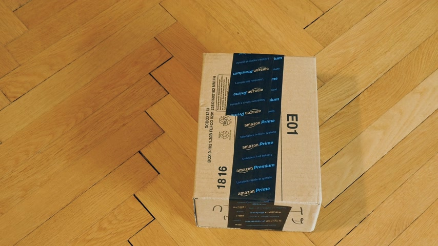 odeslání : PARIS, FRANCE - SEP 28, 2018:  Amazon Cardboard box parcel on parquet wooden floor ready for unboxing Amazon Prime is the online paid subscription service offered by Amazon.com web-commerce site