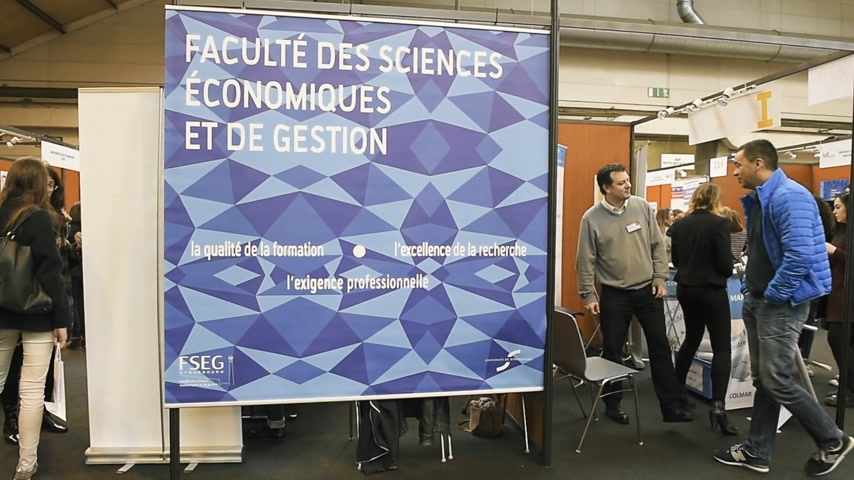 faculty : STRASBOURG, FRANCE - CIRCA 2018: Children and teens of all ages attending annual Education Fair at the stand of Faculte des sciences economiques et de gestion Stock Footage