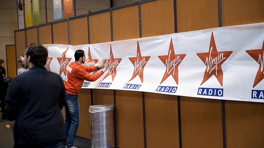 устанавливать : STRASBOURG, FRANCE - CIRCA 2018: Team arranging Virgin radio banner at exhibition stand