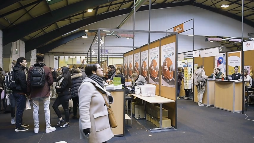インストラクター : STRASBOURG, FRANCE - CIRCA 2018: Pan over wide hall with children and teens of all ages attending annual Education Fair to choose career path and receive vocational counseling