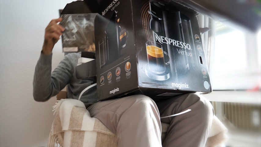 italian coffee : Paris, France - Circa 2018: Curious man unboxing unpacking in the living room new Nespresso Vertuo coffee capsules machines produced by Magimix Stock Footage